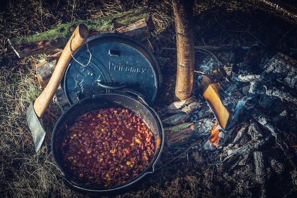 De Petromax FT4.5 Dutch oven met chili con carne handbijl links en houtskool rechts